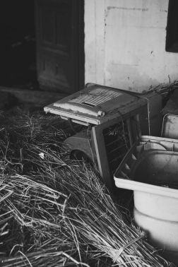 A broken air conditioning unit sits in the corner amidst discarded hay.