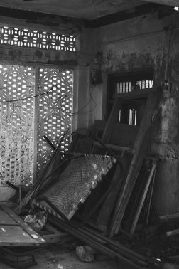 On the first floor, a classic Pakistani bed made using rope sits against a pile of wood.